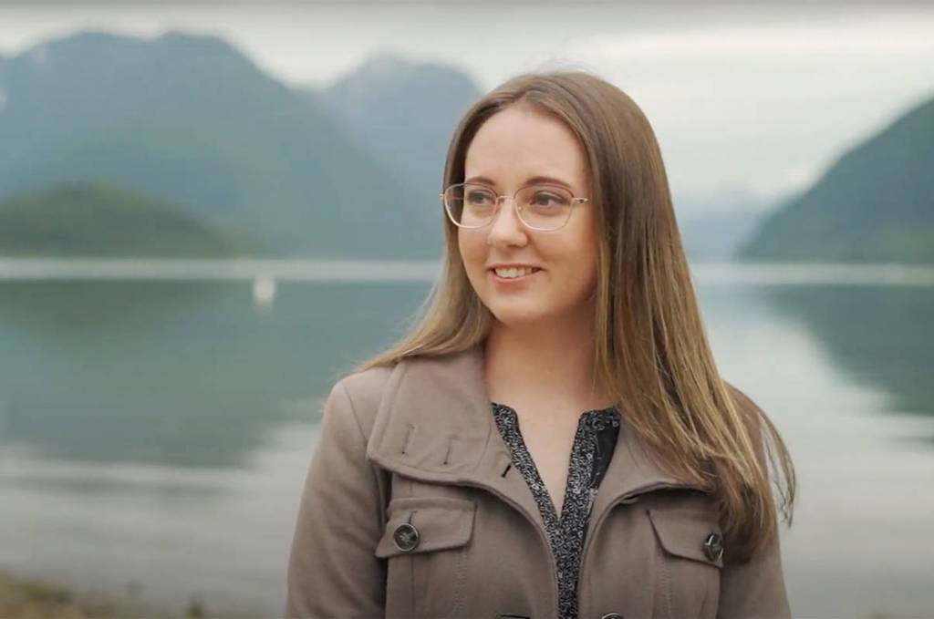 Miranda, a white female with long, light brown hair, wearing glasses. Photo is taken from the shoulders up. She is looking to the left, and standing in front of a lake and mountains